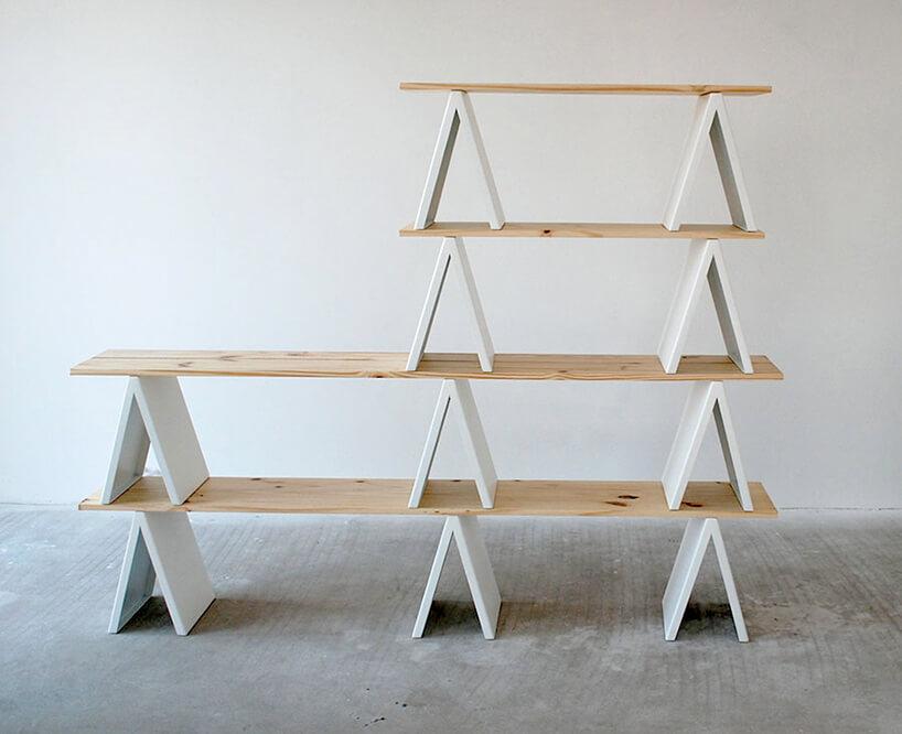 nowoczesny regał na książki stojący na białych nogach zdrewnianymi półkami
