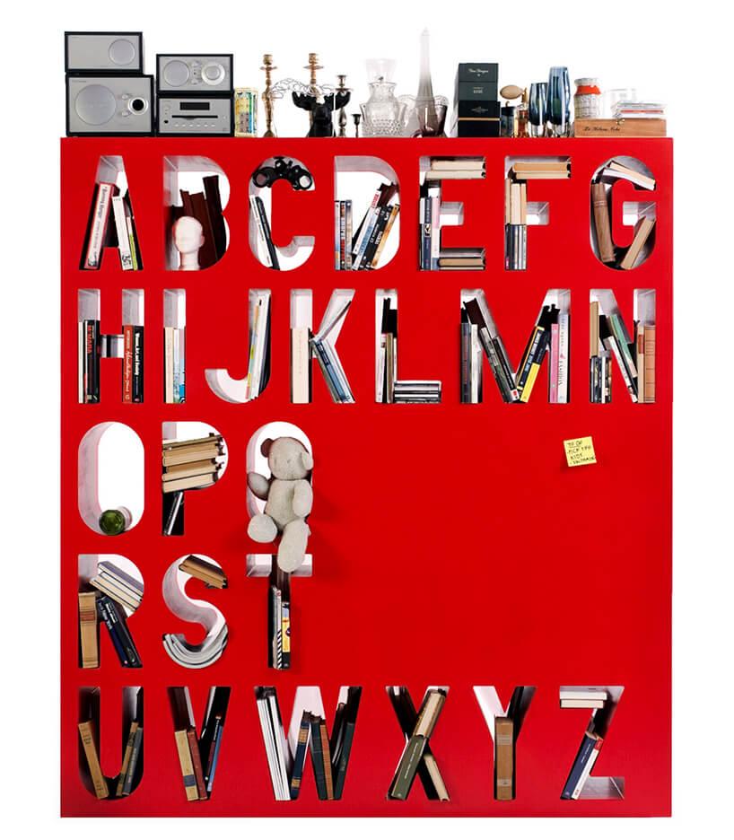 nowoczesny regał na książki czerwony zwydrążonymi literami alfabetu jako półkami zbliska