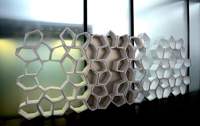 nowoczesny regał na książki zbiałych modułów na tle szklanej ściany
