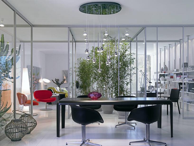 szklane ścianki działowe jako tło dla czarnego stołu ikrzeseł