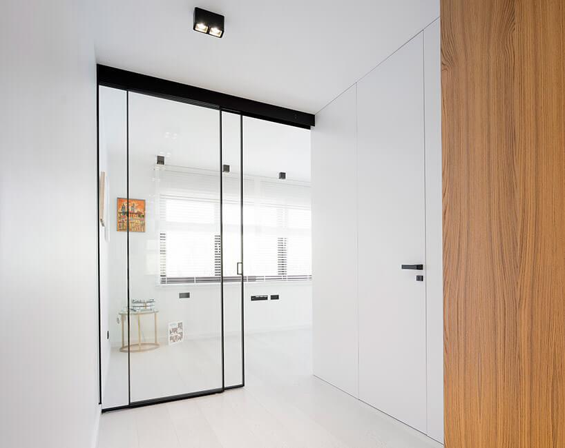 białe wnętrze ze szklanymi drzwiami wczarnej oramie