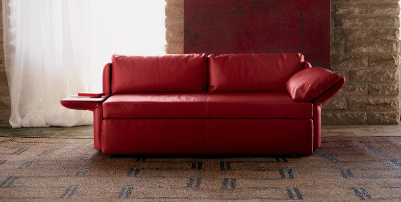 elegancka czerwona kanapa wbrązowym przestronnym pomieszczeniu