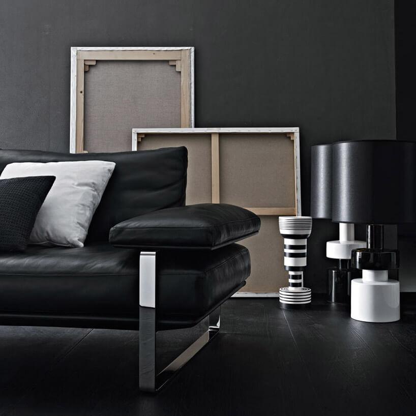 czarna sofa zczarnymi ibiałymi poduszkami brązowymi ramkami ibiałymi lampami