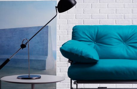 niebieska sofa z czarną lampą