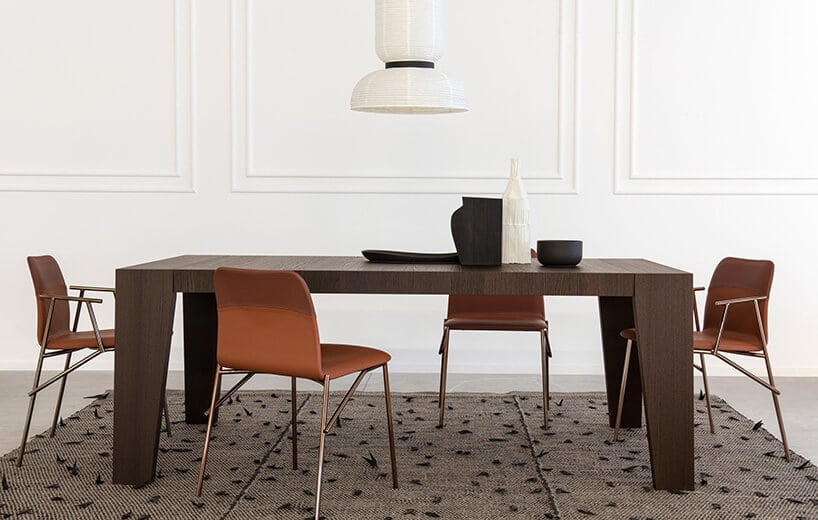 wnętrze zciemnym stołem oraz niskimi lekko pomarańczowymi krzesłami