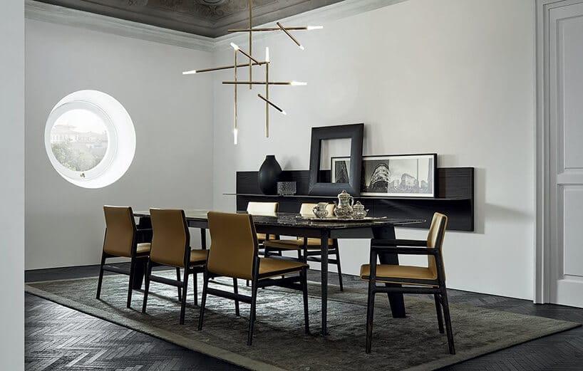 eleganckie wnętrze zokrągłym oknem oraz długim stołem iżółtymi krzesłami