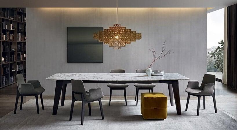 wnętrze salonu zjadalnia zszarą tapetą oraz lampą wkształcie rombu