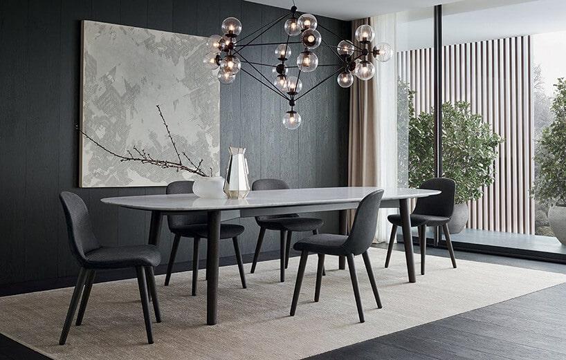 ciemno szare panele na ścianie zobrazem przy popielatym stole pod lampą zkulkami