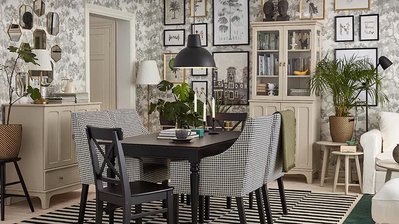 jasne wnętrze ztapetą oraz jasnymi meblami ikrzesłami zpapitą przy czarnym stole