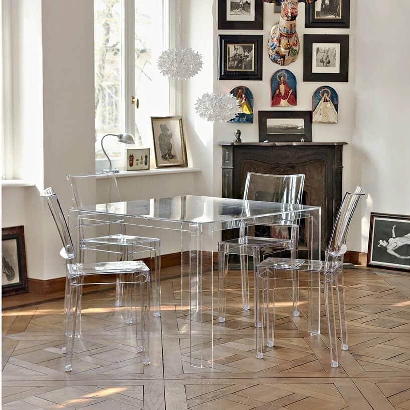 przezroczyste krzesła oraz kwadratowy stół wpomieszczeniu ze starą podłogą