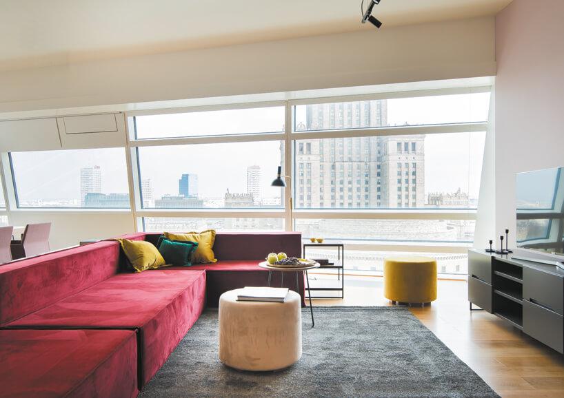 wnętrze apartamentu na Złotej 44 zprzestronnym salonem zczerwoną sofą iwidokiem na pałac kultury