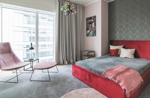 wnętrze apartamentu na Złotej 44 z dużym czerwonym łóżkiem na tle szarej ściany ze złotym wzorem i różowym fotelem