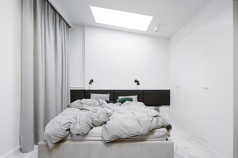 wnętrze nowoczesnej sypialni zoknem dachowym