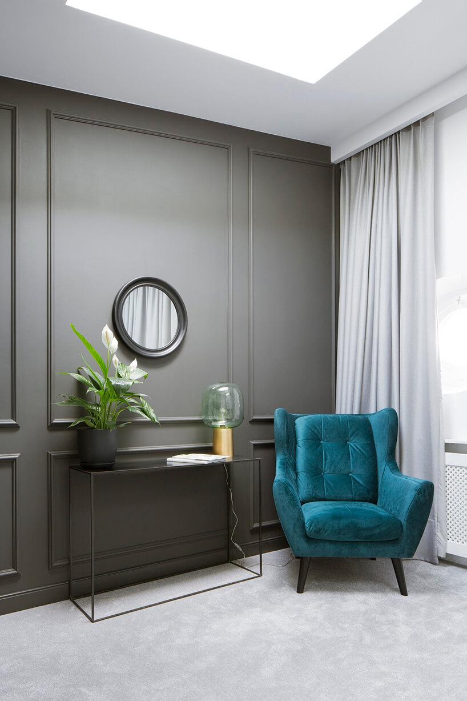 nowoczesne wnętrze zszarą ścianą iniebieskim fotelem