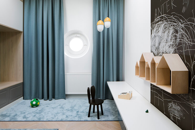 biały pokój dziecięcy zwysokimi niebieskimi zasłonami czarną tablicową ścianą