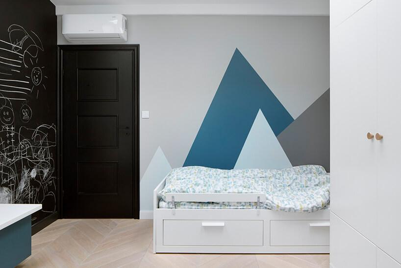 nowoczesny pokój dzieczięcy zbiałym łóżkiem czarnymi drzwiami iczarną ścianą tablicową