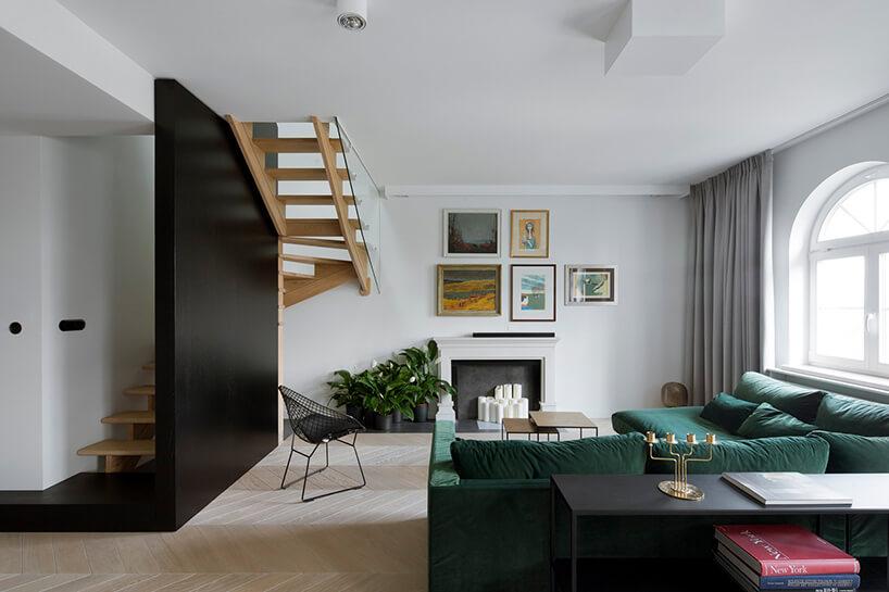 nowoczesny salon zdrewnianymi schodami zkominkiem izieloną narożną sofą