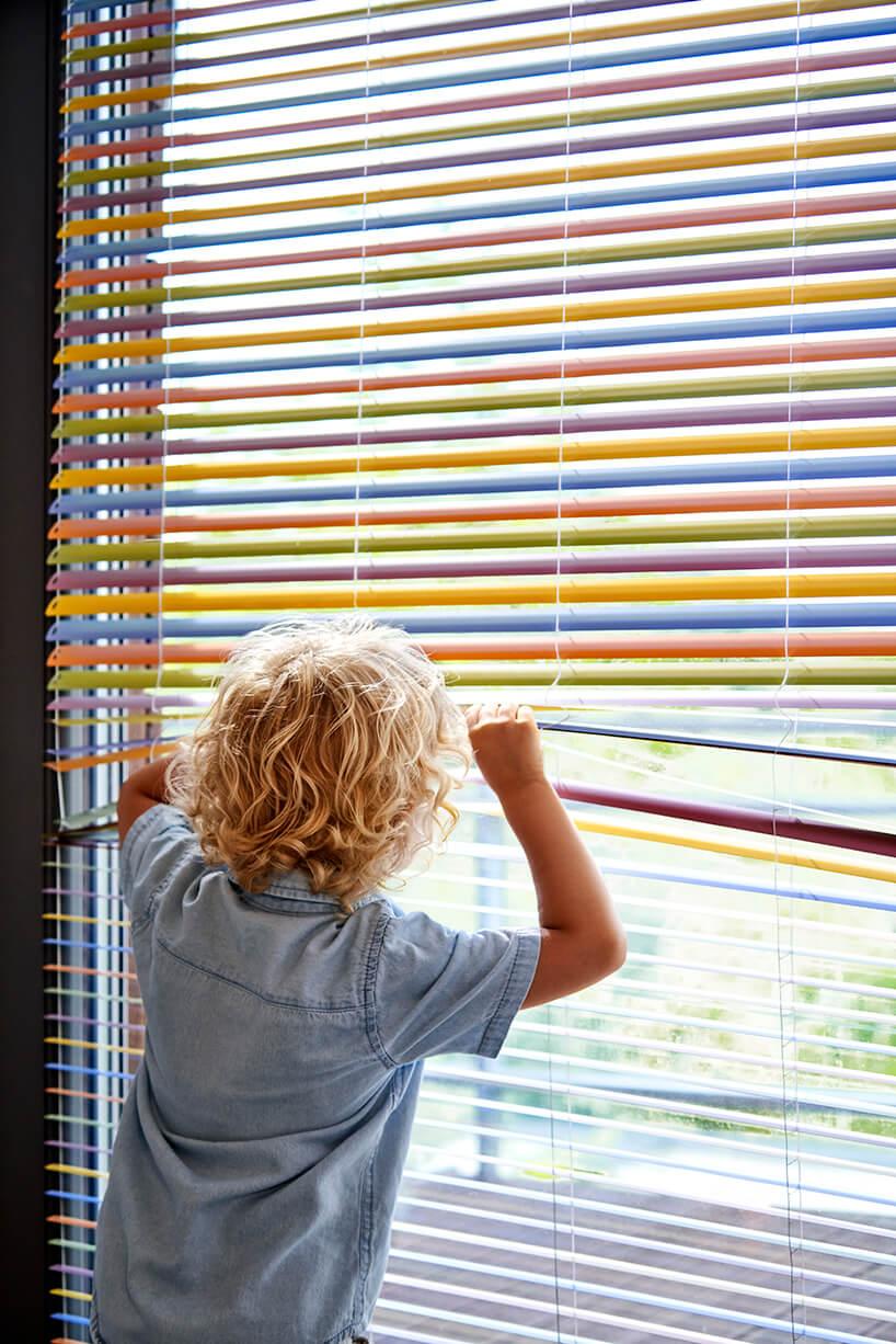dziecko patrzące przez kolorowe żaluzje aluminiowe anwis