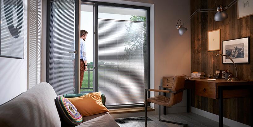 elegancki gabinet zsofą iżaluzjami aluminiowymi anwis wdużych panoramicznych oknach