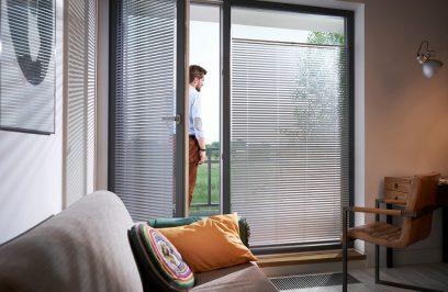 elegancki gabinet z sofą i żaluzjami aluminiowymi anwis w dużych panoramicznych oknach