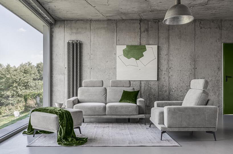 szary zestaw wypoczynkowy Merano od Gala Collezione szara sofa zwysokim oparciem obok fotela zszarym zwysokim oparciem wsalonie zsurowymi betonowymi ścianami