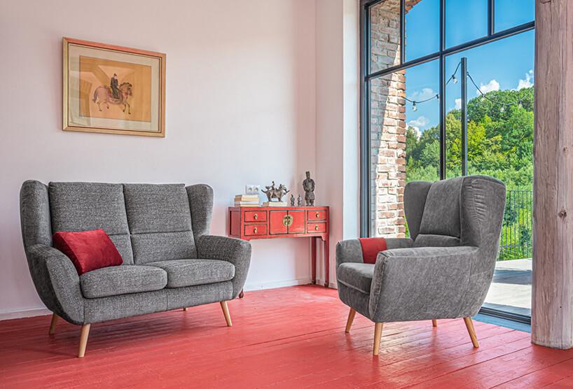 szary zestaw wypoczynkowy Forli od Gala Collezione na drewnianych nogach szara dwu osobowa sofa obok fotela na czerwonej drewnianej starej podłodze