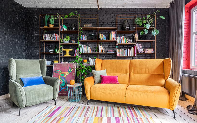 zestaw wypoczynkowy Lorien od Gala Collezione zżółtą sofą zwysokim oparciem obok jasno zielonego fotela na tle ceglanej ściany pomalowanej na czarno zregałem zksiążkami ikwiatkami