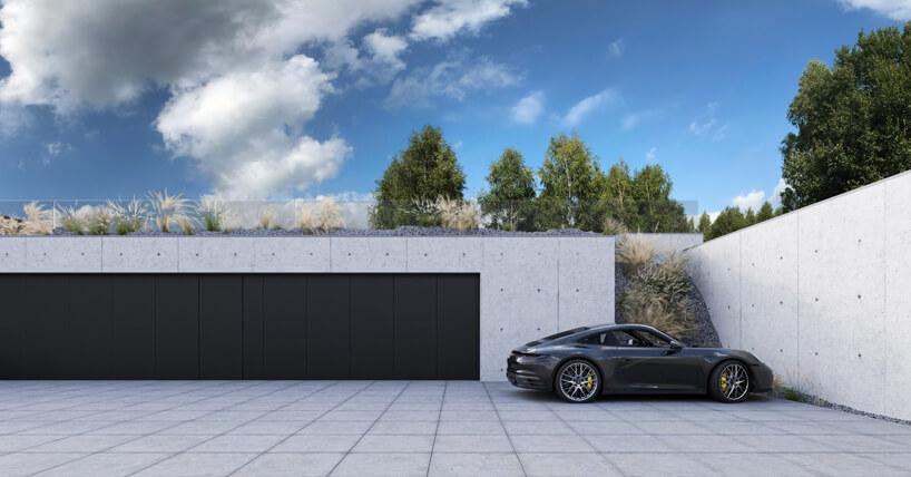 projekt domu od REFORM Architekt betonowy parking zczarnymi drzwiami ze sportowym samochodem na parkingu