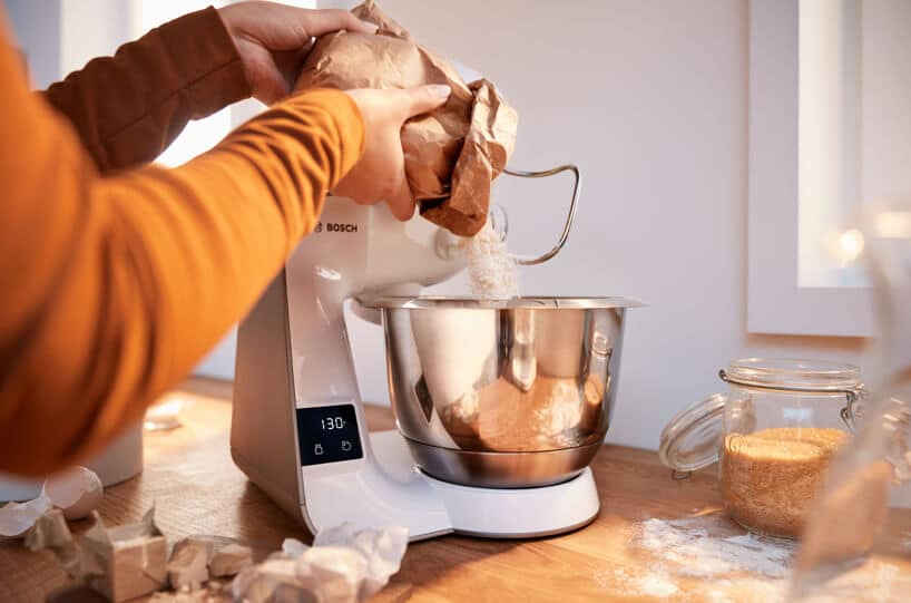 nowoczesny planetarny robot kuchenny MUM5 od Bosch na drewnianym blacie kuchennym podczas wsypywania mąki do miski