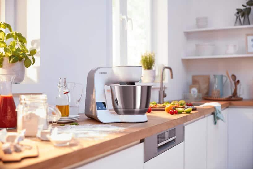 nowoczesny planetarny robot kuchenny MUM5 od Bosch ma długim drewnianym blacie wkuchni podczas przyrządzania jedzenia