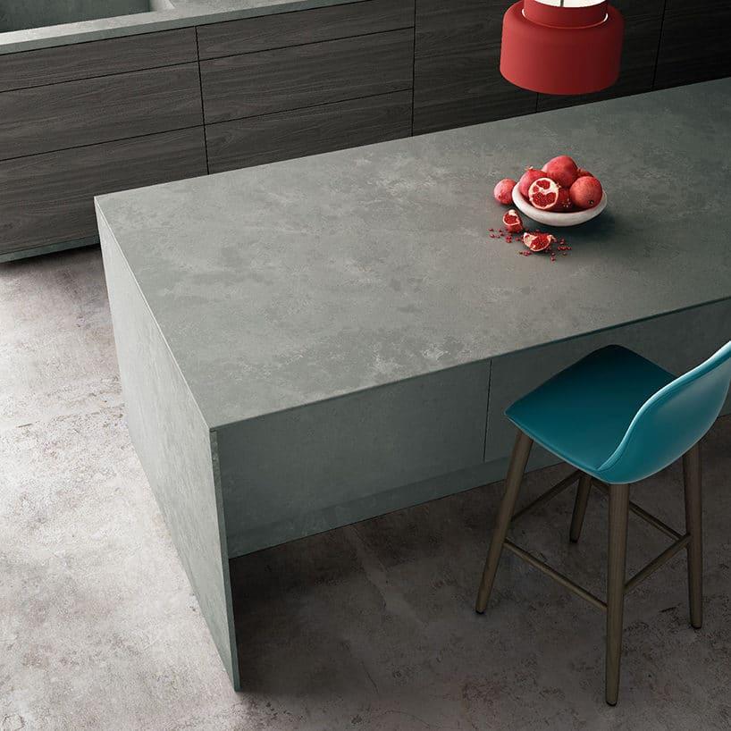 jasno szary konglomerat Silestone®Seaport od Cosentino na wyspie kuchennej na tle szarej betonowej podłogi