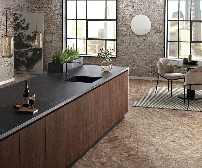 czarny konglomerat Silestone®Corktown od Cosentino na wyspie kuchennej zciemno brązowym frontem na tle ceglanych ścian