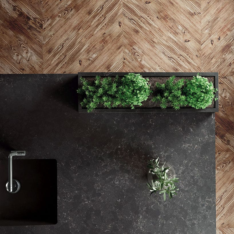 czarny konglomerat Silestone®Corktown od Cosentino zczarnym zlewozmywakiem doniczka zroślinami zgóry na tle drewnianej podłogi