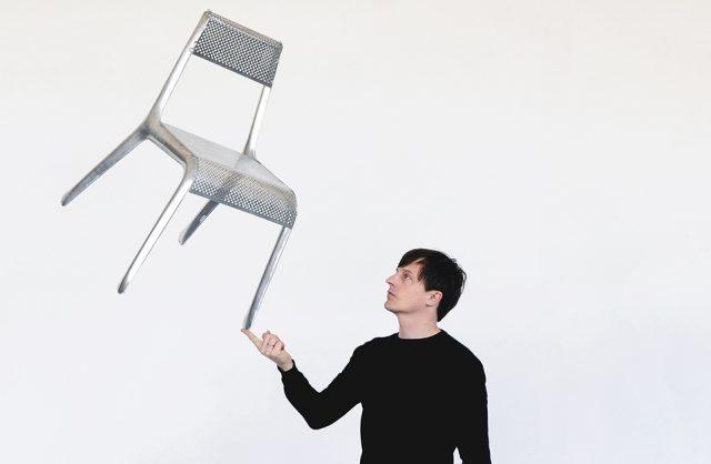 srebrne bardzo lekkie krzesło Ultraleggera trzyma na jednym palcu przez projektanta Oskara Zięte