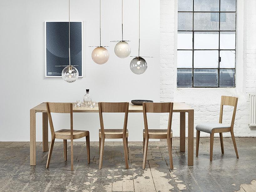 duży drewniany stół zkrzesłami wbiałym pokoju