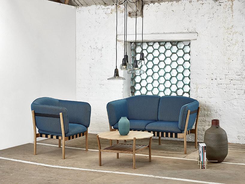 niebieska sofa zkrzesłem przy małym stoliku kawowym