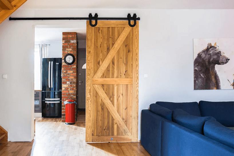 drewniane jasne drzwi zdeskami ułożonymi na ukos na czarnej szynie przesuwnej