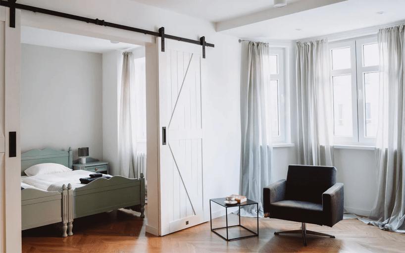 białe przesuwne drzwi zczarną listwą oraz widocznymi kółkami wpomieszczeniu zczarnym fotelem