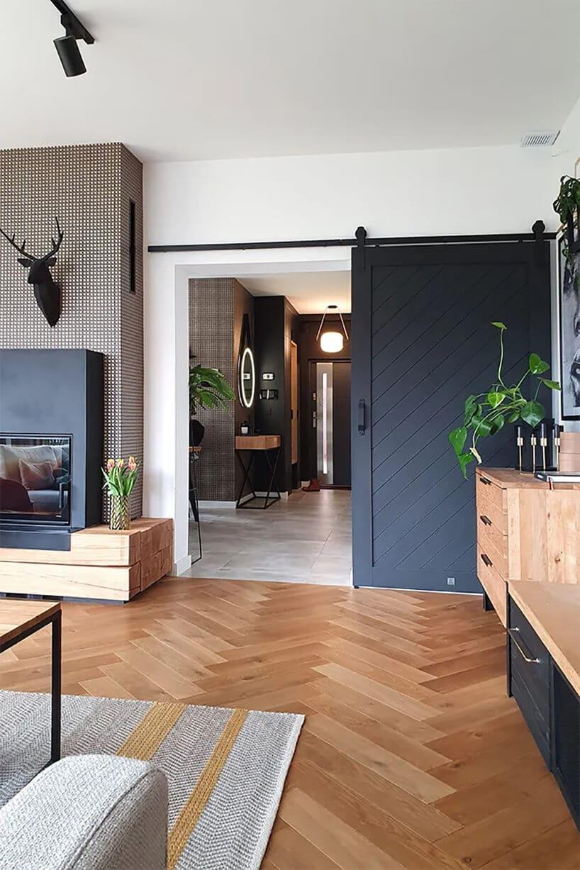 duże przesuwne drzwi na szynie pomalowane na ciemno szaro ow pomieszczeniu ze starą dębową podłogą