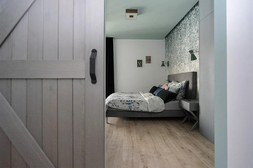 srebrno-szare drzwi przesuwne zdesek zczarną klamką iłóżkiem wtle