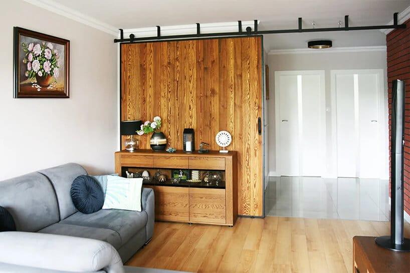 przesuwne drzwi przy komodzie obok szarej kanapy zbiałą poduszką