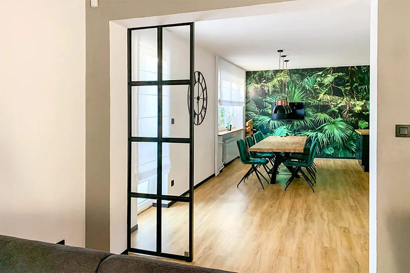 duży salon oddzielony szklanym czarnym parawanem wsalonie zdużą zielenią na ścianie
