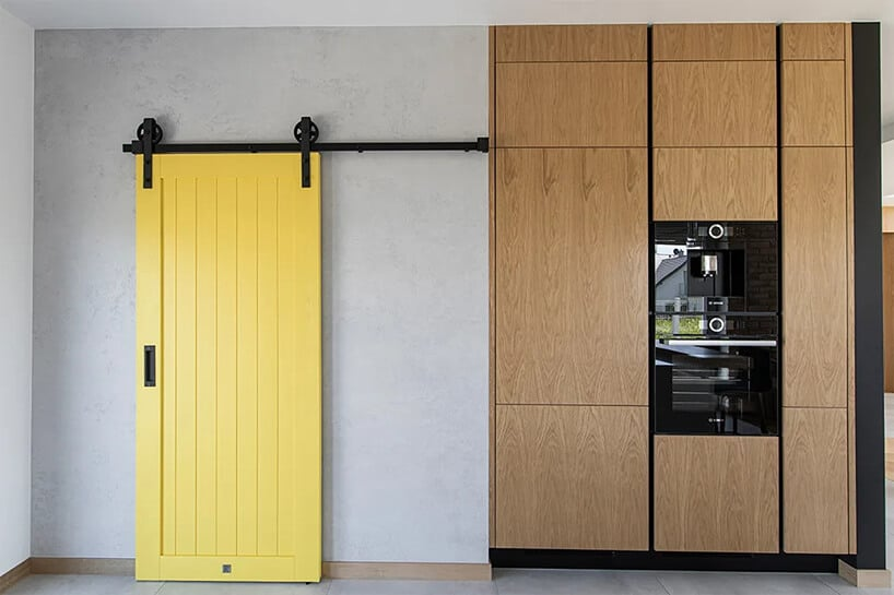 kanarkowo żółte drzwi przesuwne obok meblościanki kuchennej ze sprzętem agd