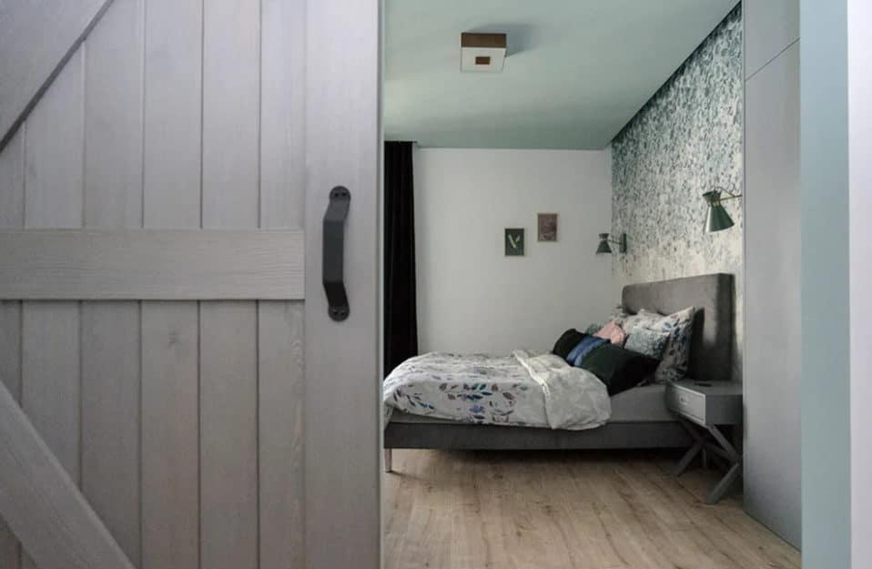 srebrno-szare drzwi przesuwne z desek z czarną klamką i łóżkiem w tle