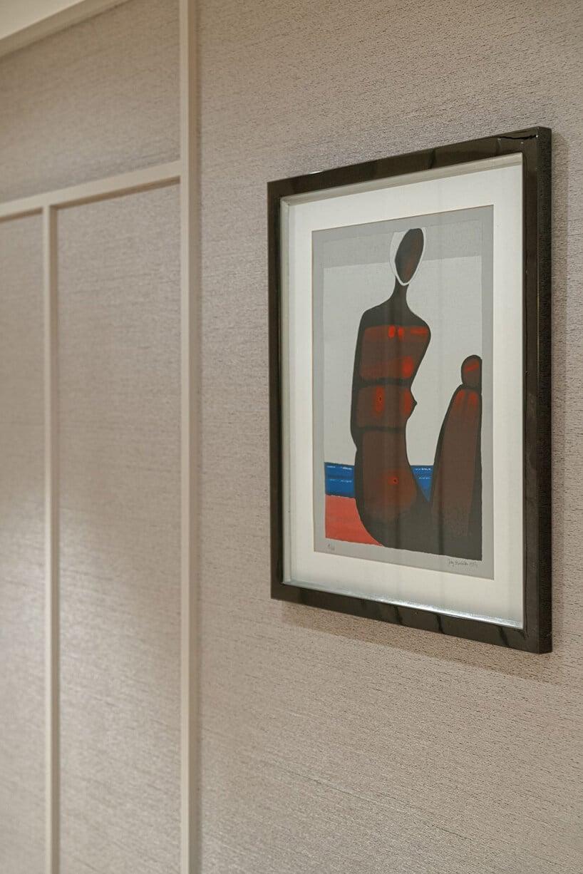 czarna rama zbiałym paspartu zobrazem na beżowej ścianie zsztukaterią