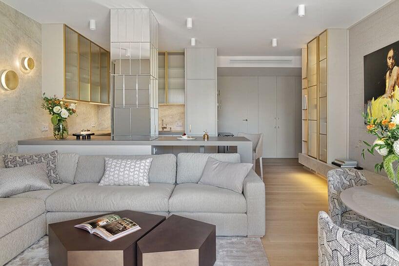 jasne wnętrze zzszarą kanapą zpoduszkami oraz drewnianym ciemnym stolikiem kawowym