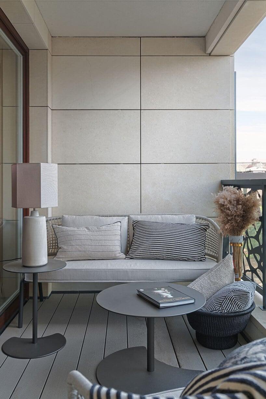 balkon zbetonowymi panelami na ścianie zwąską wersalką przy niej oraz drewniana podłoga