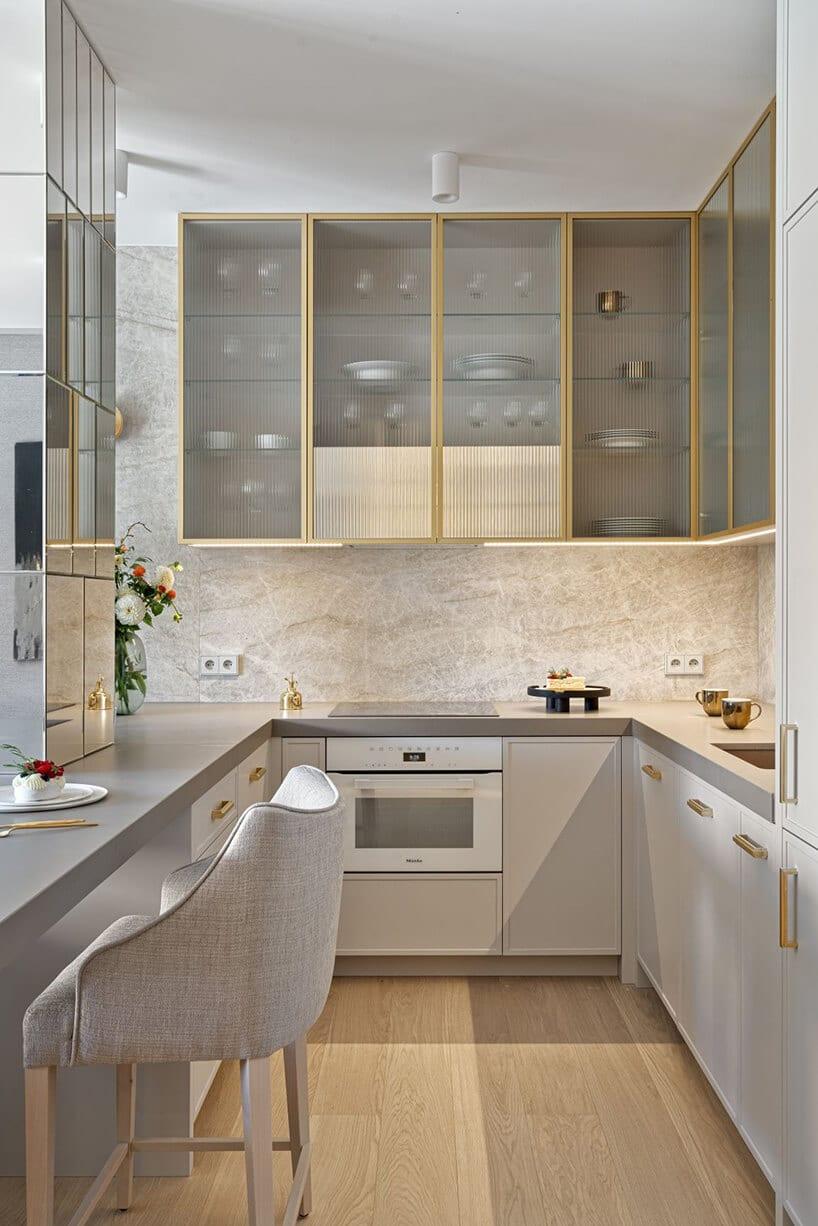 wąska kuchnia wliterę Lwjasnych kolorach oraz dębowej podłodze oraz beżowych szafkach zprzeszkleniami
