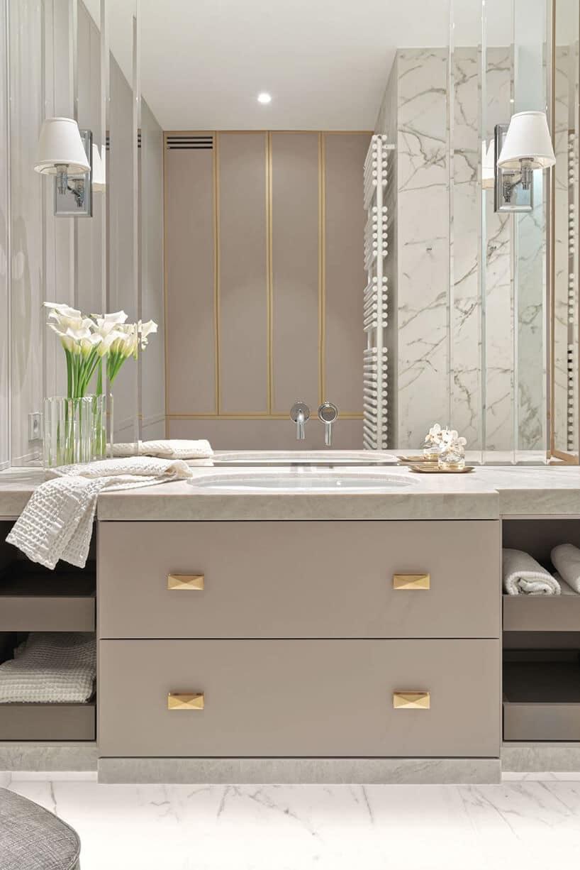 duża przestronna łazienka zbeżem oraz złotymi wstawkami oraz dużym lustrem