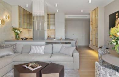 jasne wnętrze z z szarą kanapą z poduszkami oraz drewnianym ciemnym stolikiem kawowym